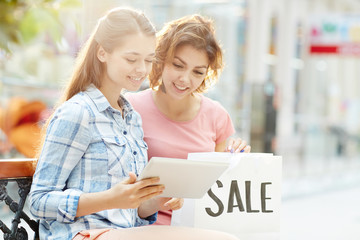 Cute girls with tablet looking through special seasonal online offers in shopping center