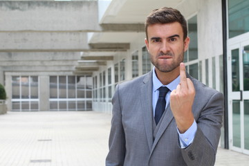 Moody businessman showing a middle finger with space for copy