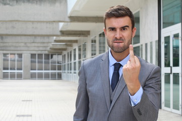 Mad businessman showing rage with middle finger