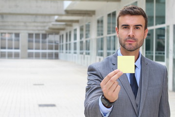 Handsome businessman showing a note