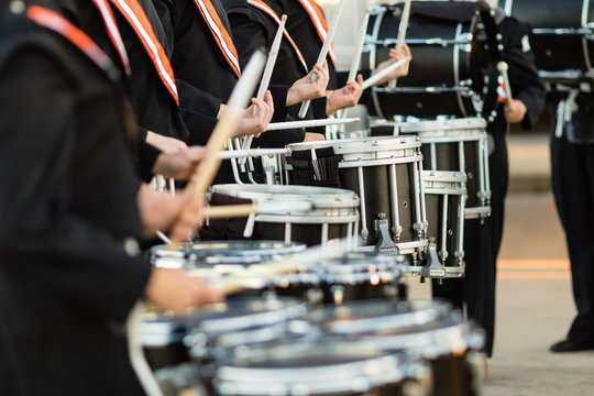 drum sticks flashing as the drumline warms up