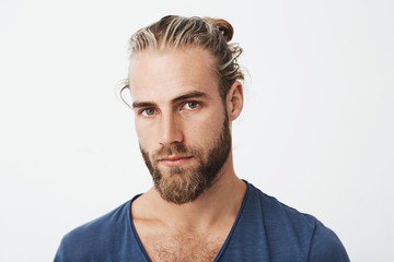 Close up of beautiful young man with stylish hairstyle and beard in blue t-shirt looking with serious expression in camera.