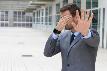 Denial concept with businessman covering his eyes
