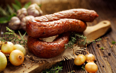 Smoked Polish sausage on a wooden rustic table with addition of fresh aromatic herbs and spices, natural product from organic farm, produced by traditional methods