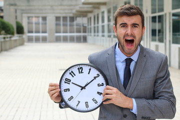 Businessman screaming while holding a big clock