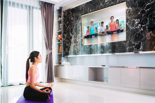 Asian lady start to training Yoga by follow coach in television in living room, in luxury mome.