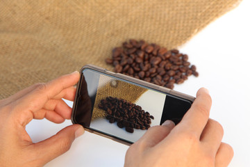 Person use camera phone to capture Roasted Coffee Beans image