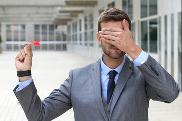Blind businessman holding a dart