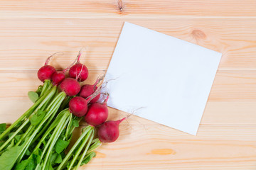 Bunch of radishes and note card on wooden background