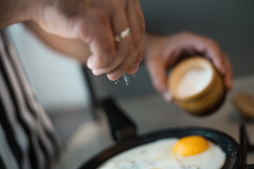 A man cook in a beautiful striped apron prepares and salt eggs in a beautiful kitchen