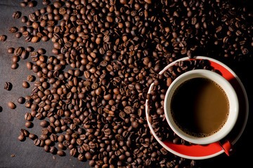 Hot coffee in red cup and coffee beans are the background.