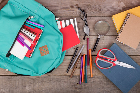 Backpack and school supplies: books, magnifying glass, notepad, felt-tip pens, eyeglasses, scissors on brown wooden table