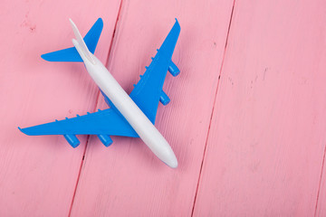 Toy plane on pink wooden background. Top view