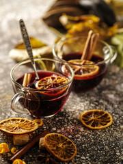 Hot mulled wine with orange, cinnamon, cardamom and anise on darken background