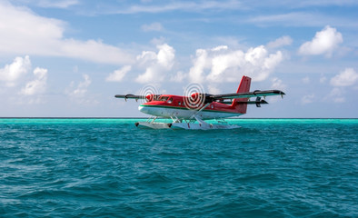 Red seaplane is taking off at the airport in Maldives