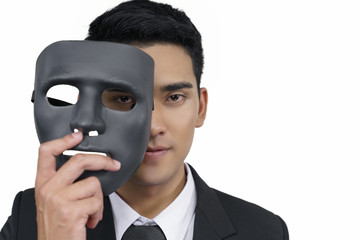 black mask with a young businessman wearing a suit, concept, spying or ambiguous