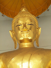 The image close up of a golden Buddha face is smiling beautifully in a temple. Buddha statue in Thailand