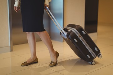 Low section of businesswoman with luggage