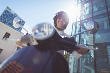 Low angle view of woman riding motor scooter