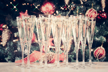 Fototapete - Glasses of champagne with Christmas tree background and sparkles. Many glasses for party. Holiday season background. Traditional red and green Christmas decoration