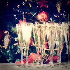 Fototapete - Filling up glasses for party. Glasses of champagne with Christmas tree background and sparkles. Holiday season background. Traditional red and green Christmas decoration
