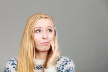 Woman having toothache touching her cheek