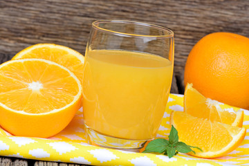 Orange juice in a glass with fruits on table