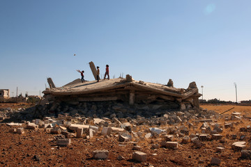 Syrian children are seen playing on a damaged house in Bosra al Sham town, south of Deraa
