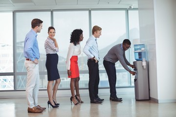 Business people standing by water cooler at office