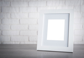 Photo frame on wood table over white brick wallpaper background