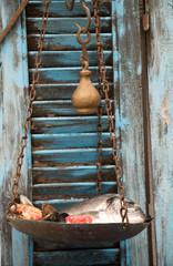 antike Handwaage mit Fisch vor einen blauen Fensterladen