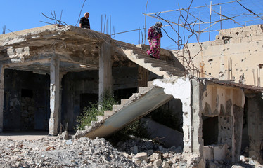 Syrian woman and man are seen in their damaged house in Bosra al Sham town, south of Deraa