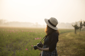 Woman tourist photographer is travel at flower field while sunset.