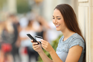 Girl paying on line with a credit card and phone