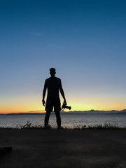 Rear view silhouetted male photographer holding camera standing by the sea at sunset