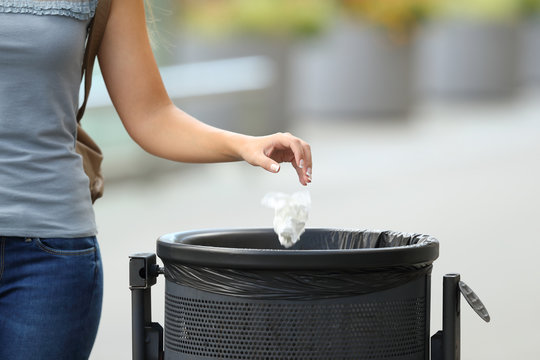Civic woman throwing garbage in a trash bin