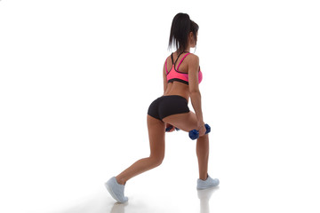 Young happy sport woman doing squats with dumbbells on gray background
