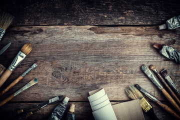 Paint tubes, brushes for painting and palette knifes on old wooden background. Top view. Flat lay. Retro toned.