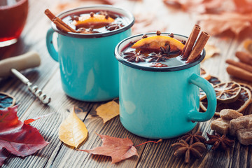 Mulled wine in blue enameled mugs with spices and citrus fruit on wooden table with autumn leaves. Retro toned.