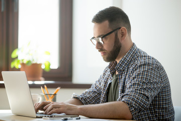 Millennial generation man in glasses and casual clothing working on laptop computer to solve a problem, concentrating on finding best solution.