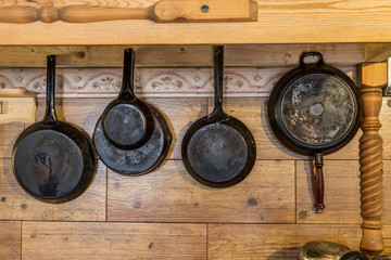 Old metallic rustic pans hanging on the wooden wall
