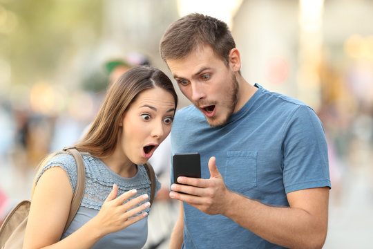 Amazed couple watching on line media in a phone