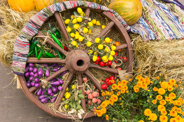 Old wooden wheel decorated with antique carpet, harvest of autumn foodstuffs and chrysanthemums