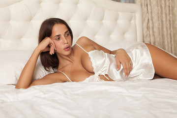 sexy brunette wearing sexy pajama on white bed