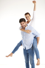 Shot of a cheerful young couple having fun together. Isolated on white background. Happy young man giving piggyback to his beautiful girlfriend.