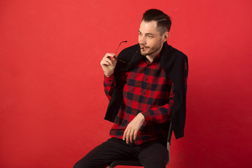 portrait of a stylish young guy in a plaid shirt sitting on a chair on a red background