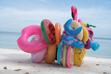 Bunch of many colorful inflatable toys isolated on the sandy beach over blue sea and sky background