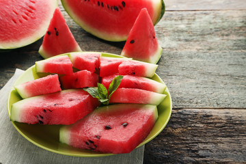 Slices of watermelons in plate on wooden table