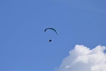 Gleitschirmflieger (Paraglider) vor blauem Himmel