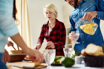 Group of modern young people standing at big table with food on it preparing dinner together for friends gathering at home, cutting vegetables and poring drinks